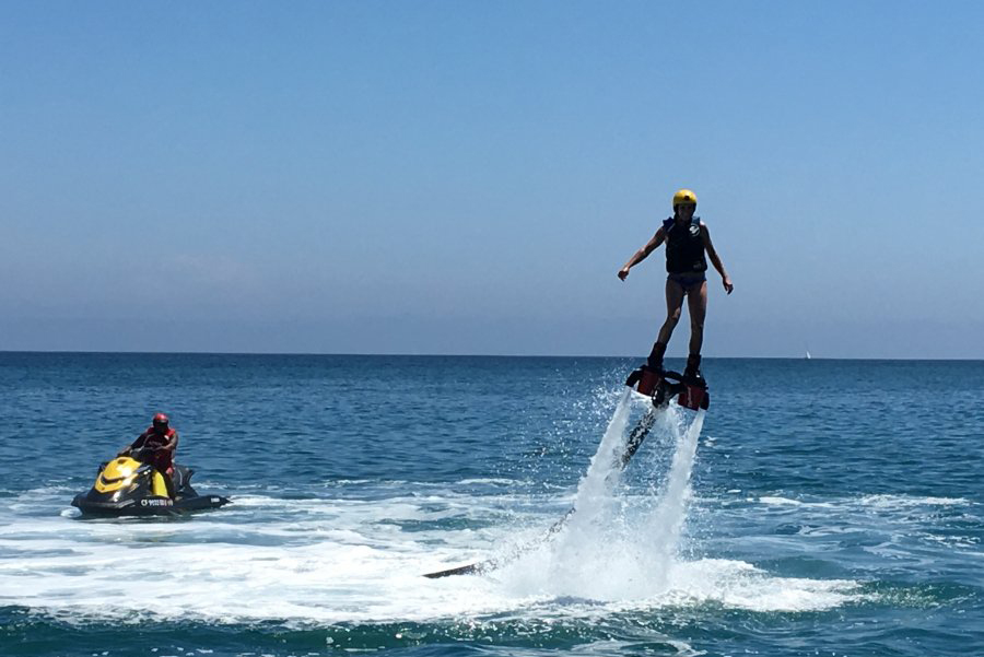 Person on a water powered action flyboard with a man on a jetski watching