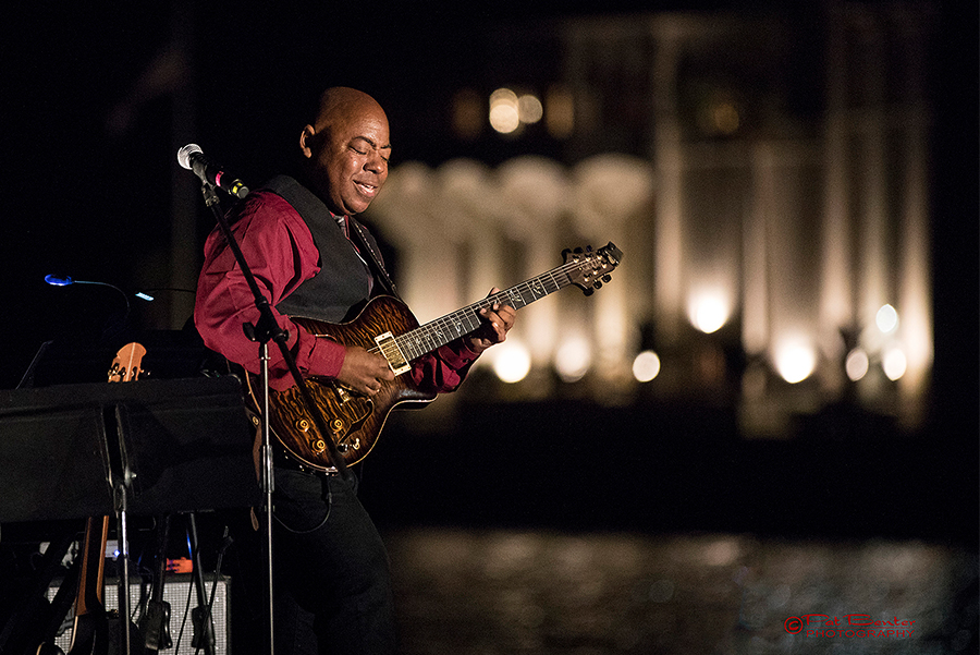 Jazz guitarist planing on Descanso beach with the Catalina casino behind him