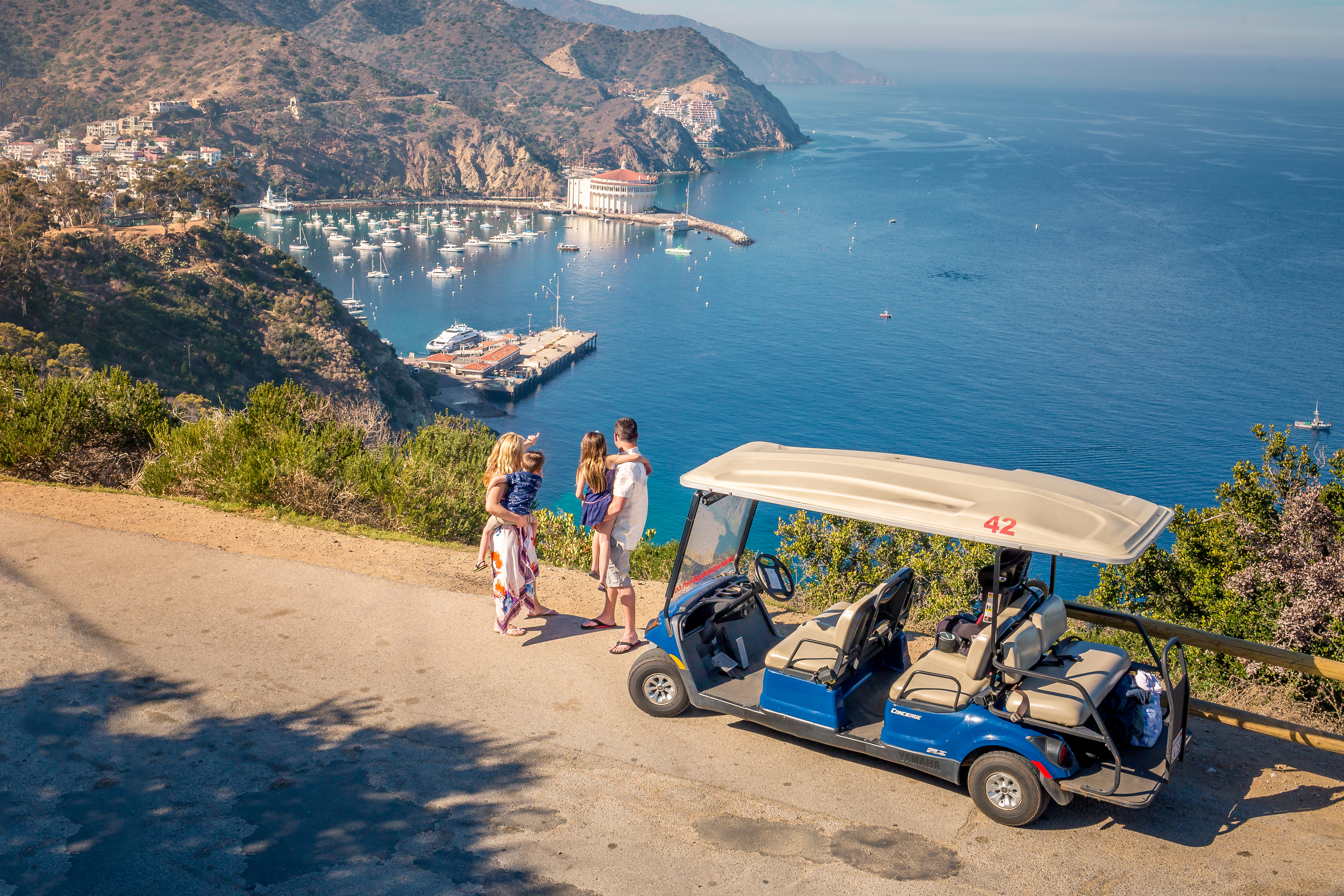 Family next to golf cart overlooking the ocean.