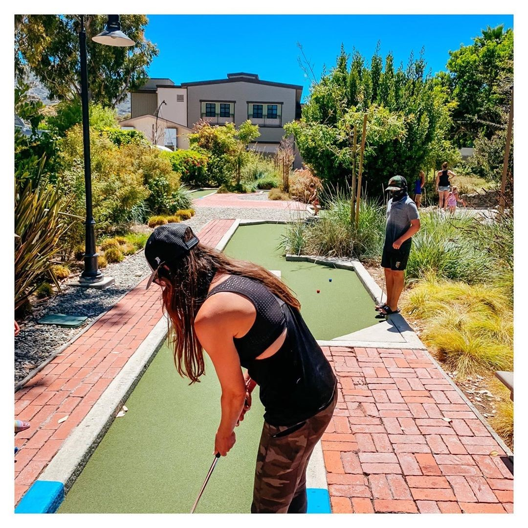 Couple playing mini golf