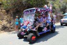 Group of people on a golf cart decorated for the 4th of july