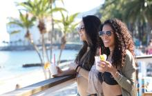 two girls enjoying a beverage on the beach